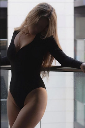 Sexy blond Irish girl in a black body against the railings